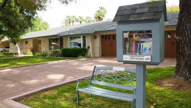 The Little Free Library outside Nancy Klatt's uptown Phoenix includes a bench for reading.