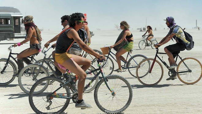People ride their bikes on the playa at Burning Man on Aug. 19, 2013, in Gerlach, Nev.