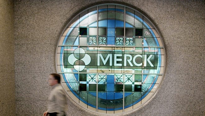 An employee walks by a stained-glass window, bearing Merck's name, as he walks to the elevator at the company's headquarters in a Whitehouse Station, N.J.