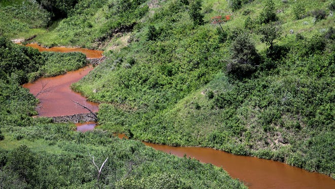 Saltwater leaks into this stream after running downhill, Thursday, July 10, 2014, near Mandaree, N.D.