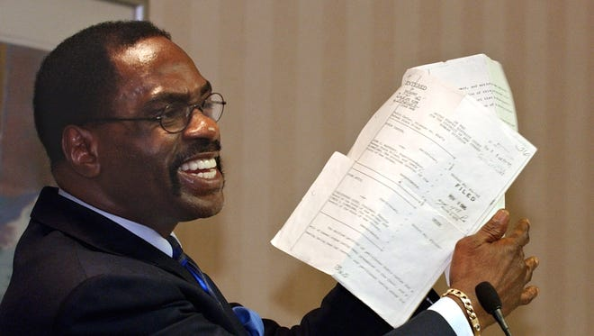 """FILE - In this Jan. 29, 2004 file photo, former boxer, Rubin, """"Hurricane"""" Carter, holds up the writ of habeas corpus that freed him from prison, during a news conference held in Sacramento, Calif. Carter, who spent almost 20 years in jail after twice being convicted of a triple murder he denied committing, died at his home in Toronto, Sunday, April 20, 2014, according to long-time friend and co-accused John Artis. He was 76."""