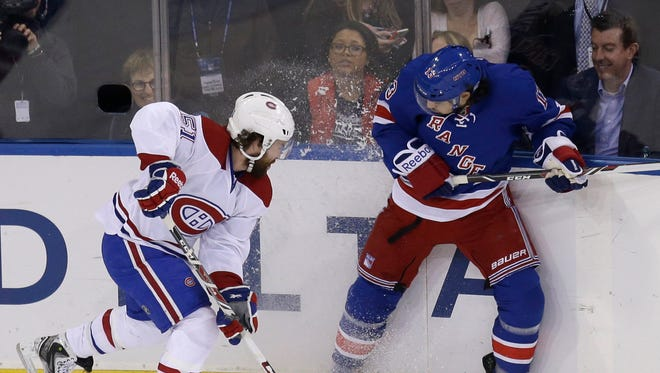 Daniel Carcillo, right, battles for the puck along the boards with the Montreal Canadiens' David Desharnais during the first period of Game 3 on Thursday night.