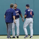 Minnesota Twins center fielder Byron Buxton (25) is checked by a team trainer and manager Paul Molitor (4) after colliding into the outfield wall on a ball hit by Texas Rangers' Rougned Odor during the first inning of a baseball game Friday in Arlington, Texas.