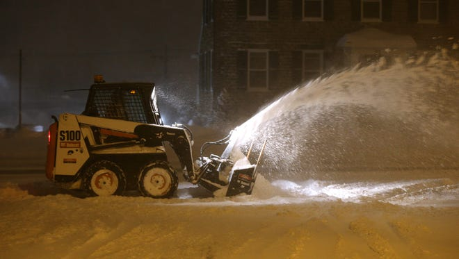 Snow continues to fall in the Rochester region as a miniplow clears sidewalks on Main Street in Webster.