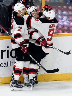 New Jersey Devils left wing Michael Cammalleri, center, celebrates with John Moore (2) and Taylor Hall (9) after scoring a goal in overtime of an NHL hockey game, Saturday, Dec. 3, 2016, in Nashville, Tenn. The Devils won 5-4.