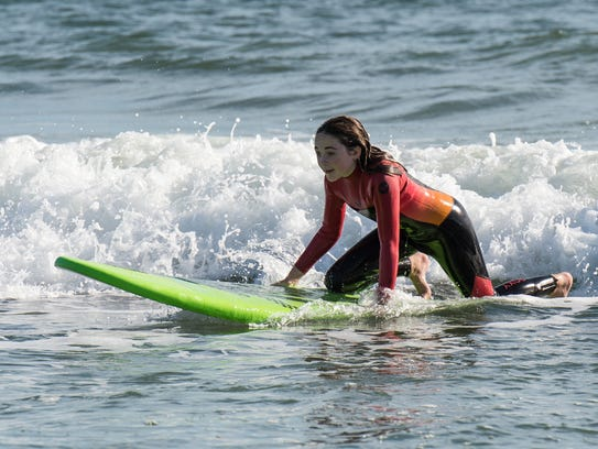 Madison Pusey rides a wave in Ocean City on Sunday,