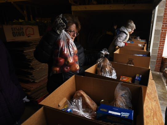 Connie Broadwater of the Salvation Army Auxiliary loads a box during the Salvation Army's distribution on Thursdays.