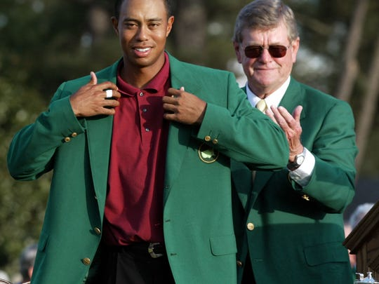 "Tiger Woods receives his 2002 Masters green jacket from Augusta National Golf Club chairman William W. ""Hootie"" Johnson. (Doug Mills, AP)"