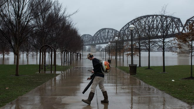 Keefe O'Brien works on blowing away water, mud and debris at Waterfront Park on Wednesday. Feb. 28, 2018