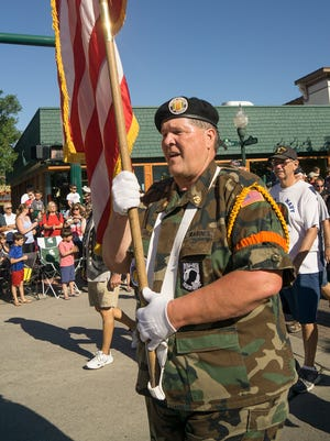 Vietnam Veterans of America member Frank Gilbo carries the colors, leading the Plymouth-Canton Chapter.