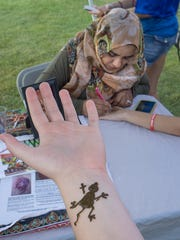 Bella Emrick shows a lizard henna design on her arm. Nausheen Razi applies a henna design to Arianna Emrick's hand and arm.