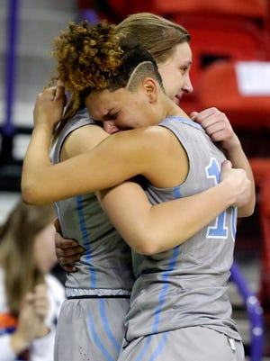 St. Thomas More's Brianna Flayter (left) and Kya Gordon hug in the closing moments of their WIAA Division 3 semifinal loss to Amherst on Thursday in Ashwaubenon.