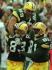 Jeff Thomason (83) is embraced by fellow Packers tight ends Mark Chmura (89) and Tyrone Davis after Thomason scored the game-winning touchdown.