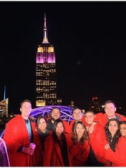 Patrons wearing red robes enjoy cocktails on the rooftop