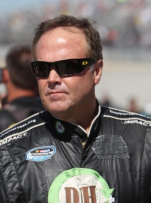 NASCAR Sprint Cup Series driver Mike Wallace walks on pit road prior to the AAA 400 at Dover International Speedway.
