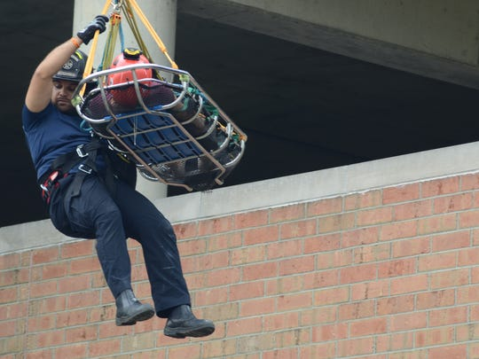 Firefighter Ryan Johnson helps guide the rescue basket to the ground Thursday, Aug. 3, 2017.