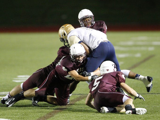 The Aquinas defense tackles Canisius's Ryan Richards during football action between the Canisius (Buffalo) Crusaders and the Aquinas Lil Irish in Rochester Friday evening, Sept. 13.