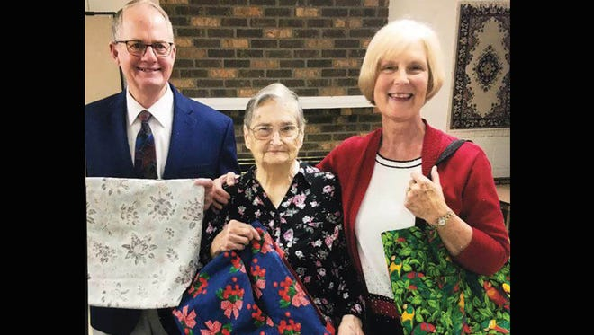 Ethel Russell (center) hands over her handmade bags to evangelists Rudy and Rose French during their recent visit to Old New Hope Baptist Church in Fairview.