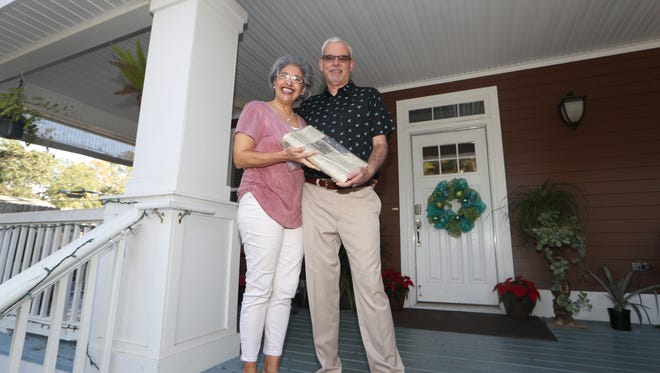 Tito Anderson and his wife Leslie, winners of the #LoveMyNewspaper contest, hold an edition of the Democrat printed on May 31, 1987, the day they were married. They have left wrapped in plastic with plans to open and read it for the first time when they retire.
