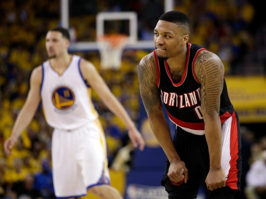 Portland Trail Blazers' Damian Lillard (0) pauses during a timeout next to Golden State Warriors' Klay Thompson, left, during the second half in Game 1 of a second-round NBA basketball playoff series, Sunday, May 1, 2016, in Oakland, Calif. Golden State won 118-106. (AP Photo/Marcio Jose Sanchez)
