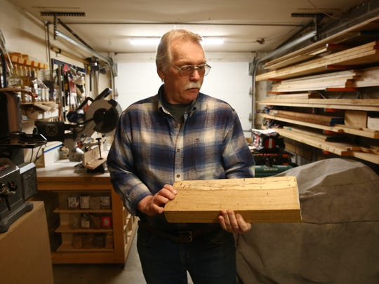 Charlie Walters examines a piece of white oak he milled from a tree that fell in his yard at his home in LaGrangeville.