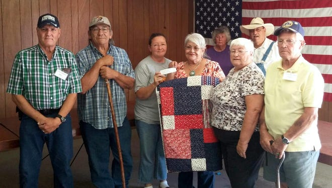 Members of the Southwestern New Mexico Transition Center gathered with quilt winners Richard and Evon Montoya for the presentation of the queen-size handmade quilt that was raffled off for the center fundraiser. Pictured in front, from left, are Bill Crosby, Richard Montoya, Cabrini Martinez, Evon Montoya, Judith Standfield and John Pace. In back are, Jacklyn Crosby and Terry Kline.