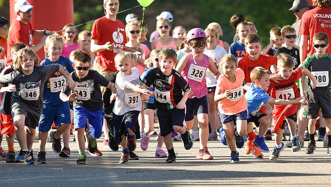 Runners in the 7 year olds category leave the starting line during the Kids Apple Duathlon Friday, May 26, in Sartell.