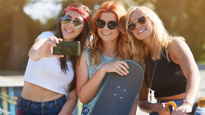 Three Millennial women taking a selfie.