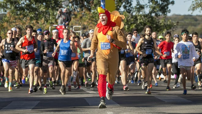 Chris Conlan leads the runners at the start of the 27th annual ThunderCloud Subs Turkey Trot in downtown Austin on Thursday, November 23, 2017.