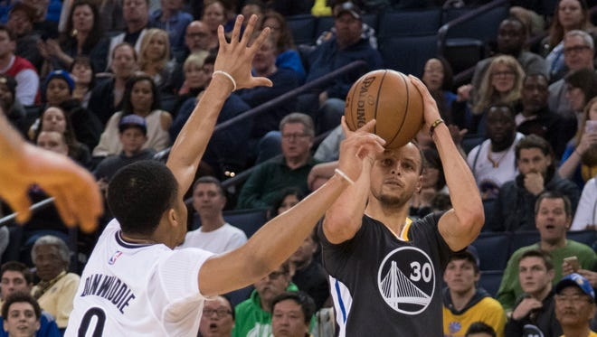 Stephen Curry shoots the basketball against Brooklyn Nets guard Spencer Dinwiddie during the second quarter at Oracle Arena.