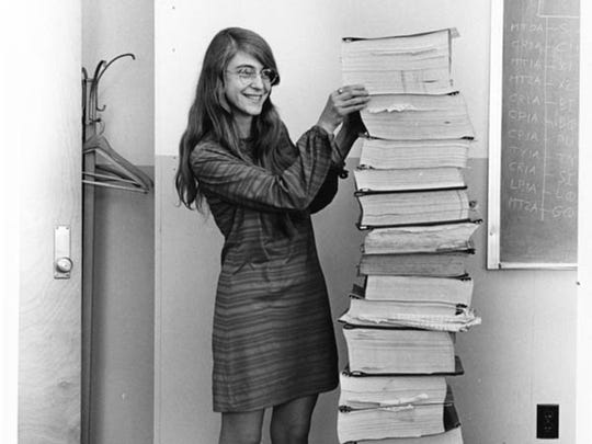 Archive photo of Margaret Hamilton standing next to a stack of Apollo Guidance Computer source code.