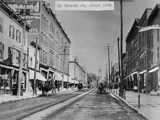 Looking up Church Street, between College and Bank. Note the hitching posts on the sidewalk on the right.