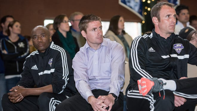 Head goalkeeper coach Thane Sutu, left, head coach James O'Connor and assistant coach Daniel Byrd watch as Louisville City FC professional soccer team members show off their new kit for fans gathered at Louisville Slugger Field in downtown Louisville where the team will play their home matches. Mar. 26, 2015