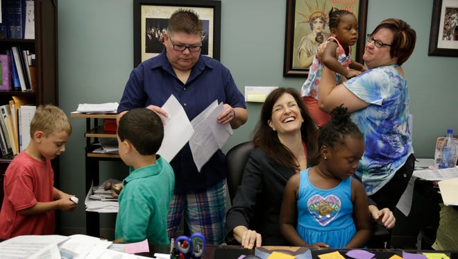 Oakland County Clerk can't help but laugh as her office is taken over by Jayne Rowse and April DeBoer and their four children of Hazel Park after they went to the Oakland County Courthouse to process their marriage certificate Friday Aug. 14, 2015.