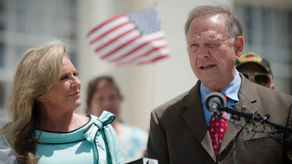 Roy Moore stands next to his wife, Kayla Moore, while announcing his Alabama Junior Senate race candidacy on April 26, 2017, in Montgomery, Ala. Moore, who was the suspended Chief Justice of the Alabama Supreme Court, said he filed paperwork to resign that position.