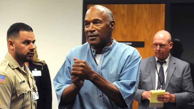 In this July 20, 2017 file photo, former NFL football star O.J. Simpson reacts after learning he was granted parole at Lovelock Correctional Center in Lovelock, Nev. Nevada's parole board says it didn't consider O.J. Simpson's 1989 conviction for misdemeanor spousal abuse when it granted him parole in July because it wasn't listed in the federal clearinghouse of FBI crime data.