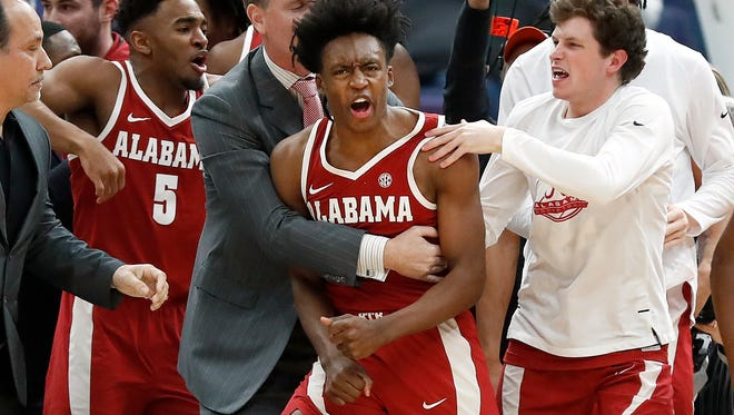 Alabama's Collin Sexton, center, is congratulated by teammates after making a game-winning basket at the buzzer to defeat Texas A&M 71-70 in an NCAA college basketball game at the Southeastern Conference tournament Thursday, March 8, 2018, in St. Louis.