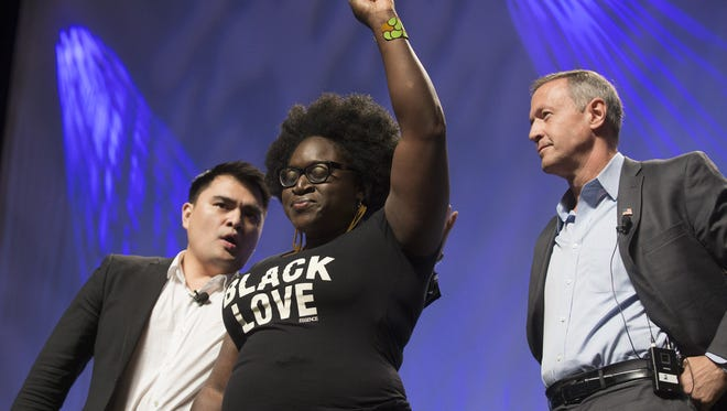 Tia Oso (left), a Phoenix resident with the Black Alliance for Just Immigration, interrupts moderator Jose Antonio Vargas and Gov. Martin O'Malley during the Netroots Nation convention on July 18, 2015.
