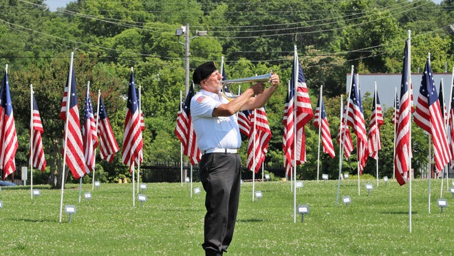 """Richard Doyle, a member of the Veterans' Honor Guard, played """"Taps"""" during the annual dedication ceremony for the Field of Flags held in downtown Jackson on Saturday, June 16, 2018."""