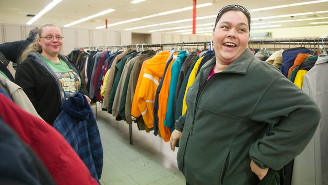 Cynthia Parton of Knoxville debates between two coats during KARM's 30th annual Coats for the Cold coat drive in Knoxville Saturday, Dec. 5, 2015.