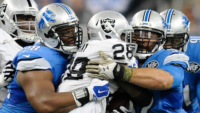 The Lions' C.J. Wilson, left, and Haloti Ngata bring down the Raiders' Latavius Murray in the second quarter.