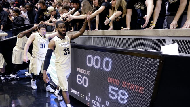 Purdue guard Rapheal Davis (35) and guard Dakota Mathias (31) celebrates with fans following a 60-58 win over Ohio State in an NCAA college basketball game in West Lafayette, Ind., Wednesday, Feb. 4, 2015. (AP Photo/Michael Conroy)