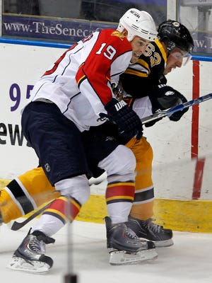 Florida's Marty Reasoner (19), left, puts a shoulder to Boston's Brad Marchand in the corner during exhibition NHL hockey action between the Boston Bruins and the Florida Panthers at the Blue Cross Arena in 2010.
