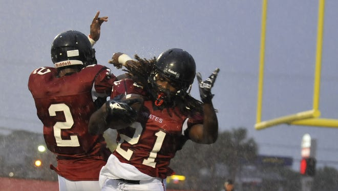 Palm Bay?s Sekai Lindsay (21) celebrates his touchdown with teammate Twonnie Pollard (2) during Friday night?s game.  BRIAN CURL FOR/ FLORIDA TODAY (  Prep Sports )