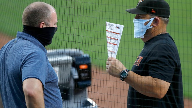 Baltimore Orioles director of baseball administration Kevin Buck, left, and field coordinator Tim Cossins wear masks to protect against COVID-19 as they talk during an intrasquad game at baseball training camp Tuesday, July 14, 2020, in Baltimore.