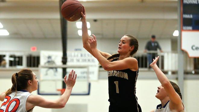 Lebanon High School guard Kelsey Winfrey (1) passes the ball in between two Hornets defenders during a Feb. 9, 2017 high school basketball game between the Lebanon High School Yellowjackets and the Hillcrest High School Hornets.