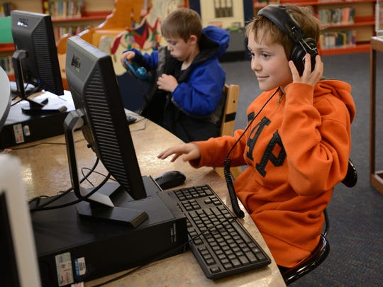 Cadel Condit (left), 6, and his brother T.J., 8, use the computers in the children's area at the Salem Public Library. As part of the remodel, computers were moved to the circular counter near the main desk. The counters are tall enough for wheelchairs.