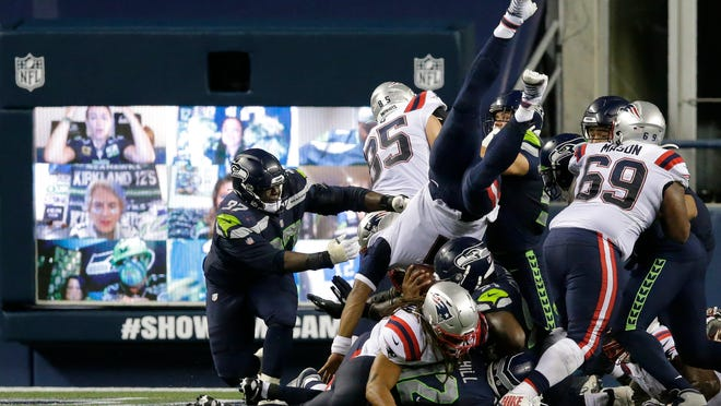 New England Patriots quarterback Cam Newton dives with the ball but is stopped near the goal line as the clock expires in the fourth quarter of an NFL football game against the Seattle Seahawks, Sunday, Sept. 20, 2020, in Seattle. The Seahawks won 35-30. In the background, fans cheer via remote video links on a video monitor.