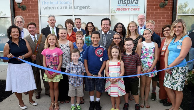 Mayor Barbara Wallace (left) and Robert Timmons, president of the Washington Township Chamber of Commerce (second from left), join John DiAngelo (center) and administrators and physicians from Inspira and local children at the ribbon cutting for a new Urgent Care center in Washington Township..