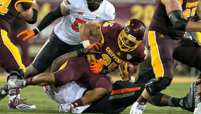 Sep 3, 2015; Mount Pleasant, MI, USA;  Central Michigan Chippewas running back Devon Spalding (25) is brought down by the Oklahoma State Cowboys defense during the 1st quarter at Kelly/Shorts Stadium.